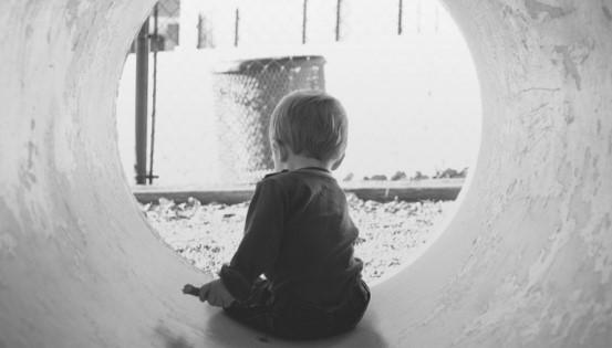 czarno-białe zdjęcie małego chłopca siedzącego w betonowej rurze